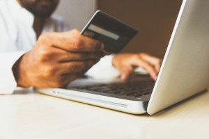 Ein Arzt nutzt eine Kreditkarte und tippt am Lapptop