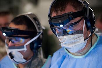 Zwei Ärzte mit Schutzbrillen und Stirnlampe forschen