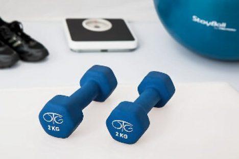 Zwei kleine blaue Hanteln im Vordergrund. Im Hintergrund Sportschuhe, eine Wage und ein Gymnstikball